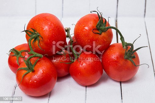 Close view of a tasty pile of wet tomatoes isolated on a white wooden background.