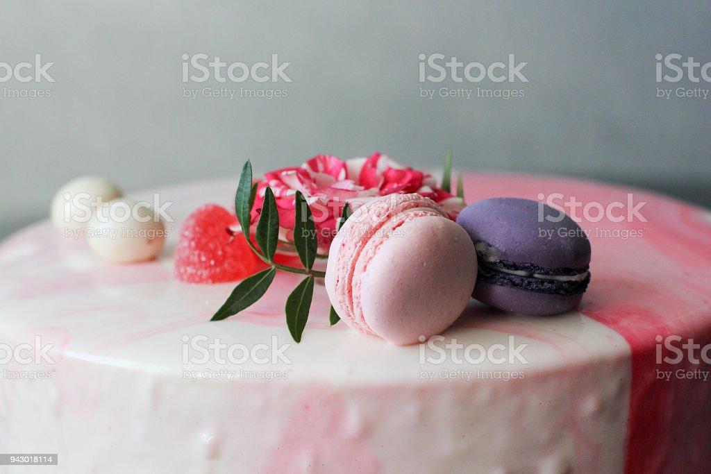 Smakelijke roze zelfgemaakte taart gedecoreerd door rose en macarons foto