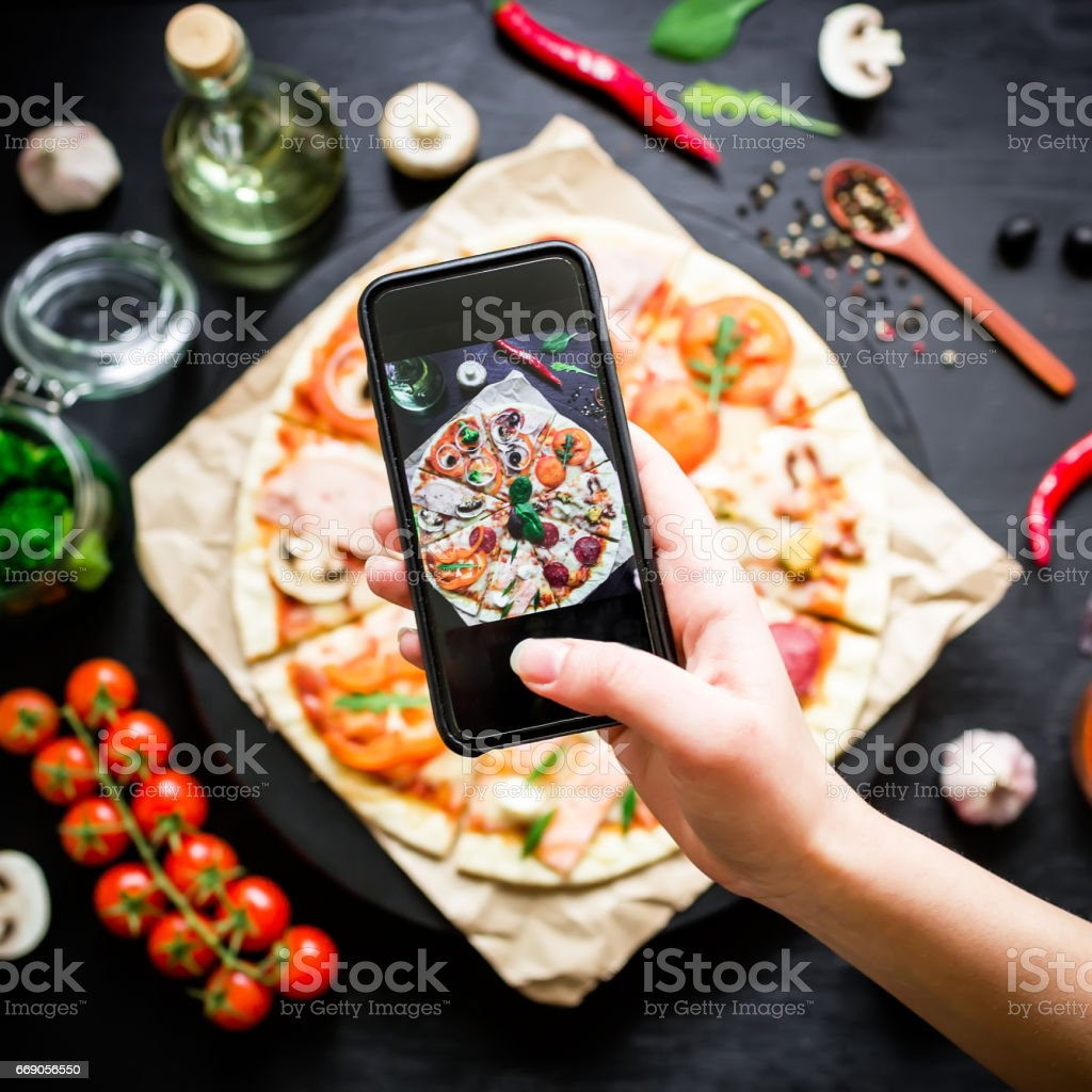 Tasty pizza with ingredients, spices and mobile phone on black background. Flat lay, top view. The phone takes pictures of food royalty-free stock photo