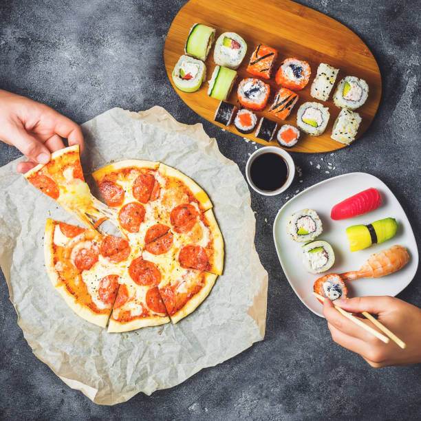 Leckere Pizza mit Salami, Set Sushi Rollen und Hände nehmen Nahrung. Dunklen Hintergrund. Flach legen, Top Aussicht. – Foto
