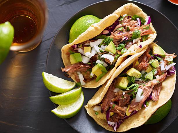 tasty pork street tacos with onion, cilantro, and avocado - tacos photos et images de collection