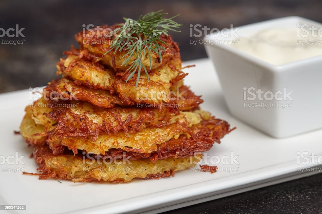 Tasty potato pancakes or latke with sauce stock photo