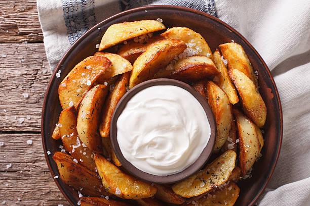 Tasty potato wedges with mayonnaise on a plate closeup. Horizontal stock photo