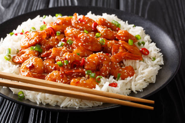 Tasty prawns with garlic, chili, sesame seeds and green onions served with rice close-up in a plate. horizontal stock photo