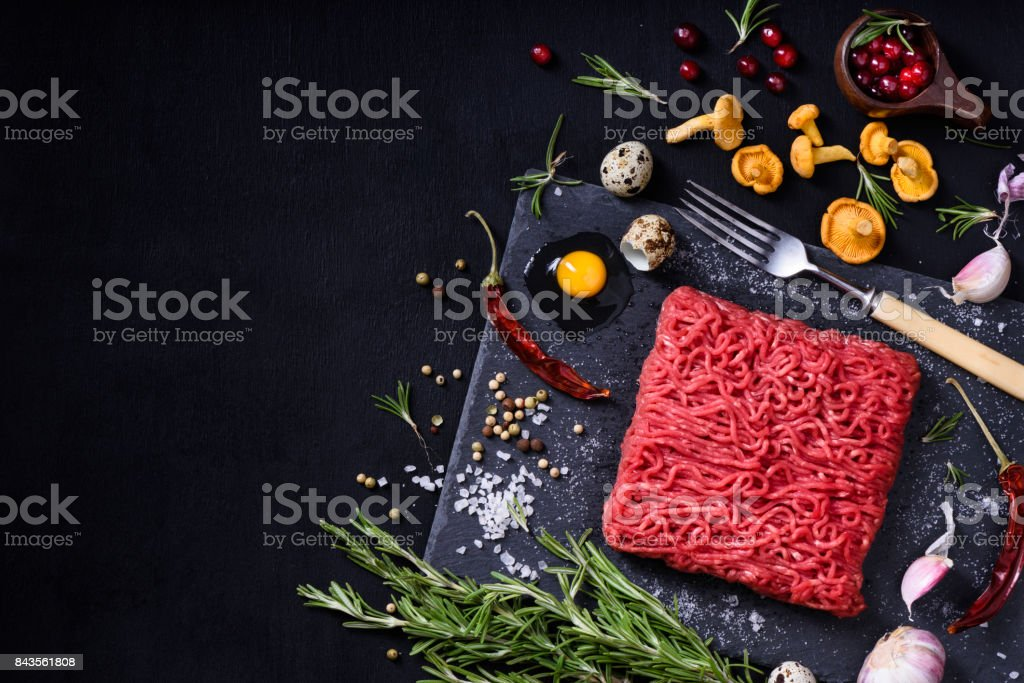 Tasty raw veal or beef meat on black table. Cooking ingredients. stock photo