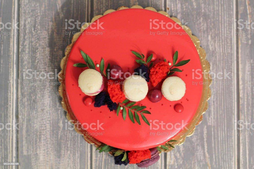 Smakelijke rode zelfgemaakte cake versierd met rode snoepjes en macarons foto