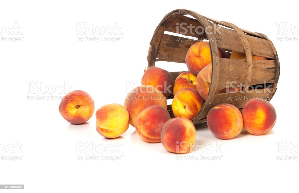 Tasty Ripe Peaches in a Tipped Basket royalty-free stock photo