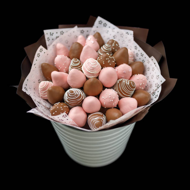Tasty ripe strawberries in brown and pink chocolate in the form of a bouquet on a black background. stock photo