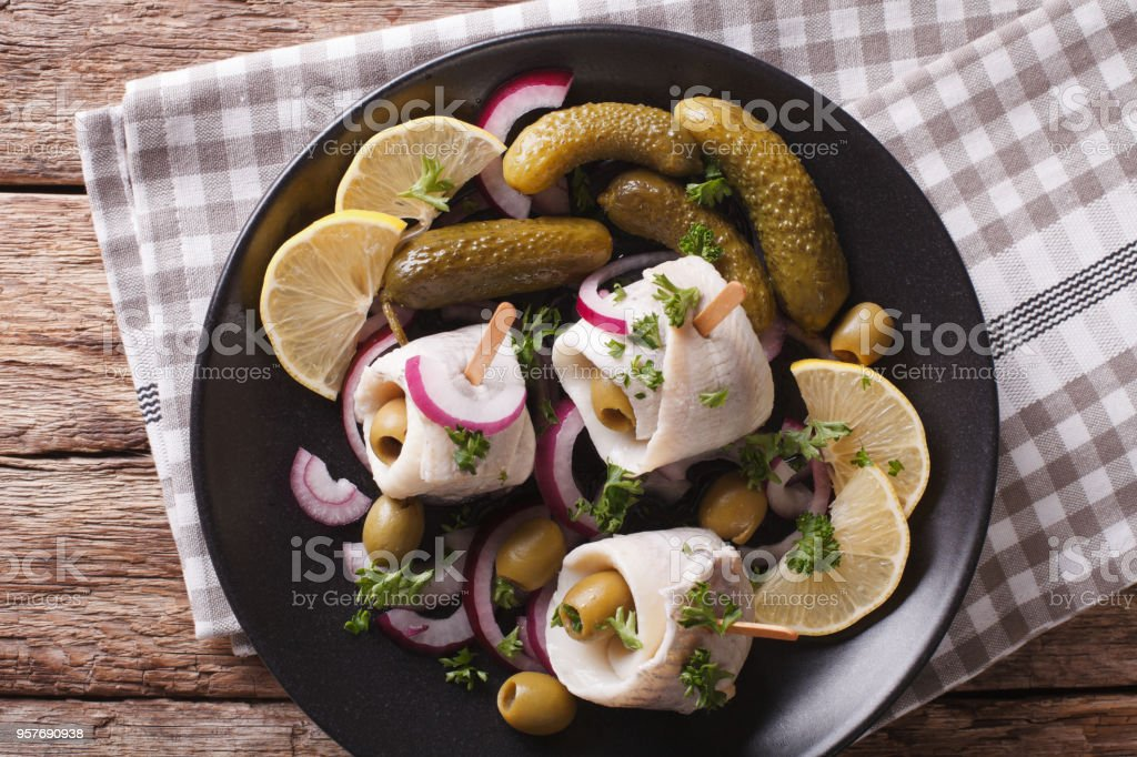 Tasty rollmops stuffed olives, onions, pickles and lemon close-up on a plate. horizontal top view stock photo