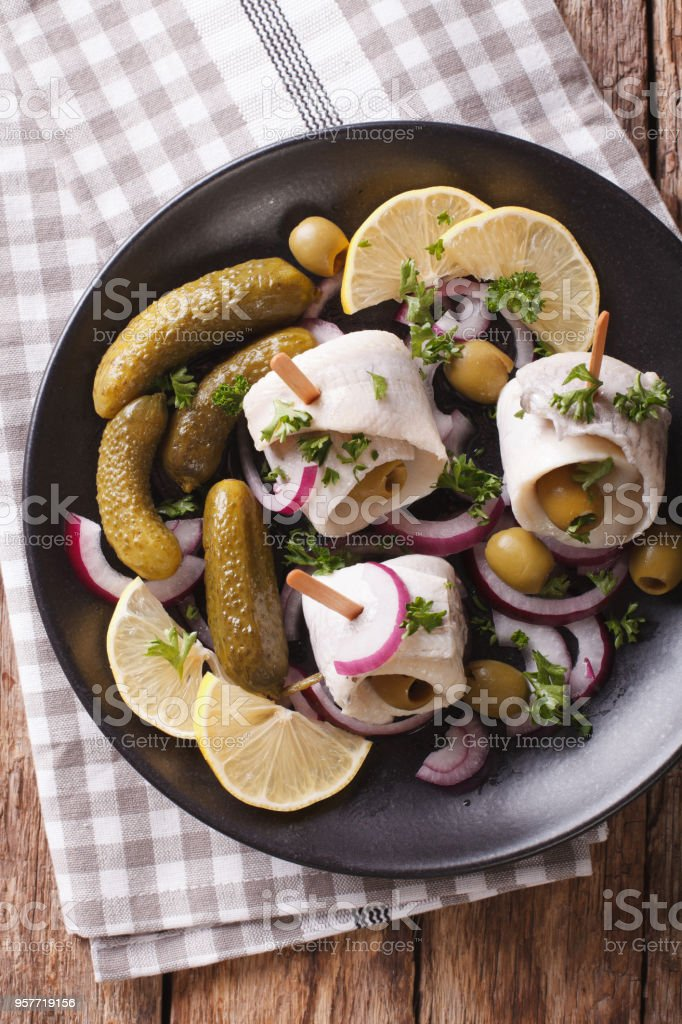 Tasty rollmops stuffed olives, onions, pickles and lemon close-up on a plate. Vertical top view stock photo
