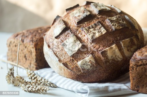 913749618istockphoto Tasty rustic bread and ears of wheat on table 832655306