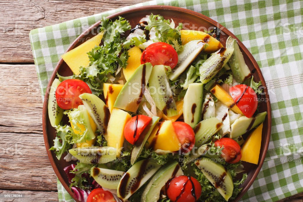 Tasty Salad Of Mango Avocado Kiwi Lettuce Tomato Closeup On A