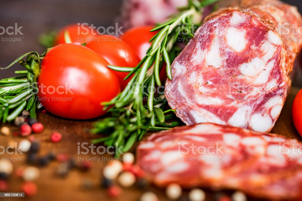 Tasty salami with tomatoes and peppercorn close royalty-free stock photo