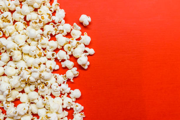 Tasty salted popcorn isolated on red background stock photo