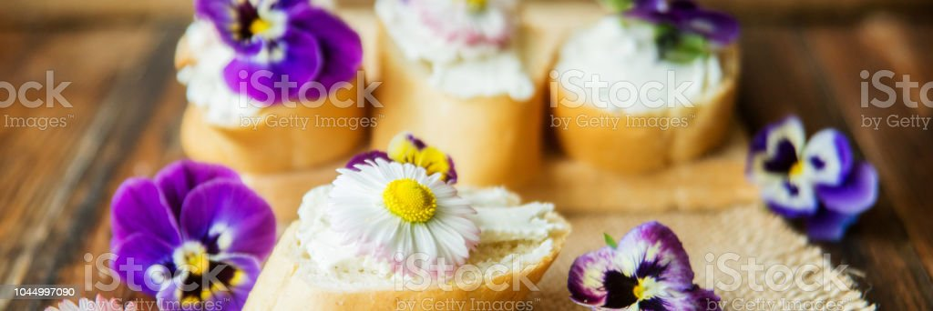 Tasty sandwich with avocado boiled eggs, pumpkin seed and edible viola flowers in a white board. healthy food stock photo