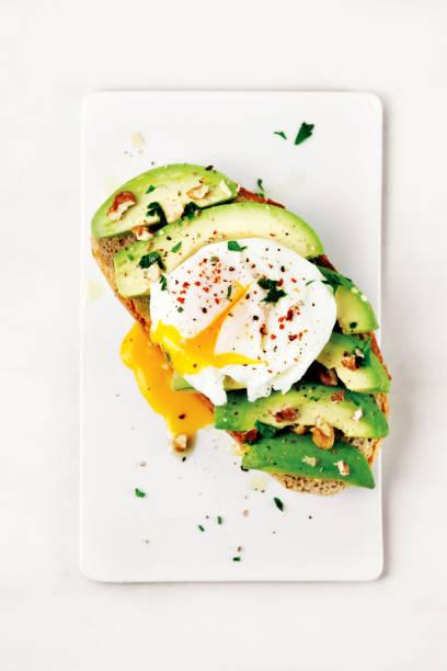 saboroso sanduíche com ovo pochê e abacate - torrada - fotografias e filmes do acervo