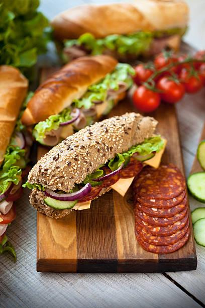 köstliche sandwiches auf einem holztisch - käse wurst salat stock-fotos und bilder
