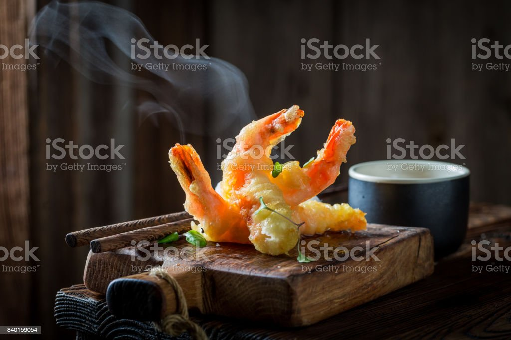 Tasty shrimp in tempura with red sauce on black background stock photo