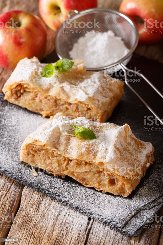 Tasty slice of apple strudel with powdered sugar and mint closeup. vertical stock photo
