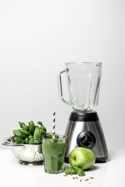 smakelijke smoothie in glas met stro in de buurt van verse spinazie bladeren, appel en blender op wit - mixer stockfoto's en -beelden