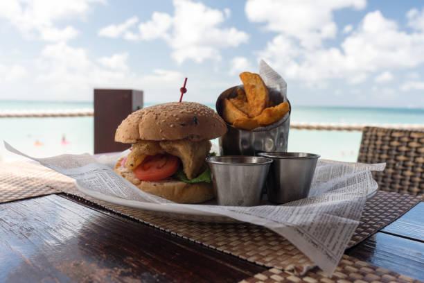 smakelijke specialist hamburger met aardappel wiggen - newspaper beach stockfoto's en -beelden