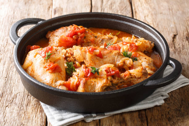 Tasty spicy rabbit stew in tomato sauce with white wine and herbs close-up in a pan. horizontal stock photo