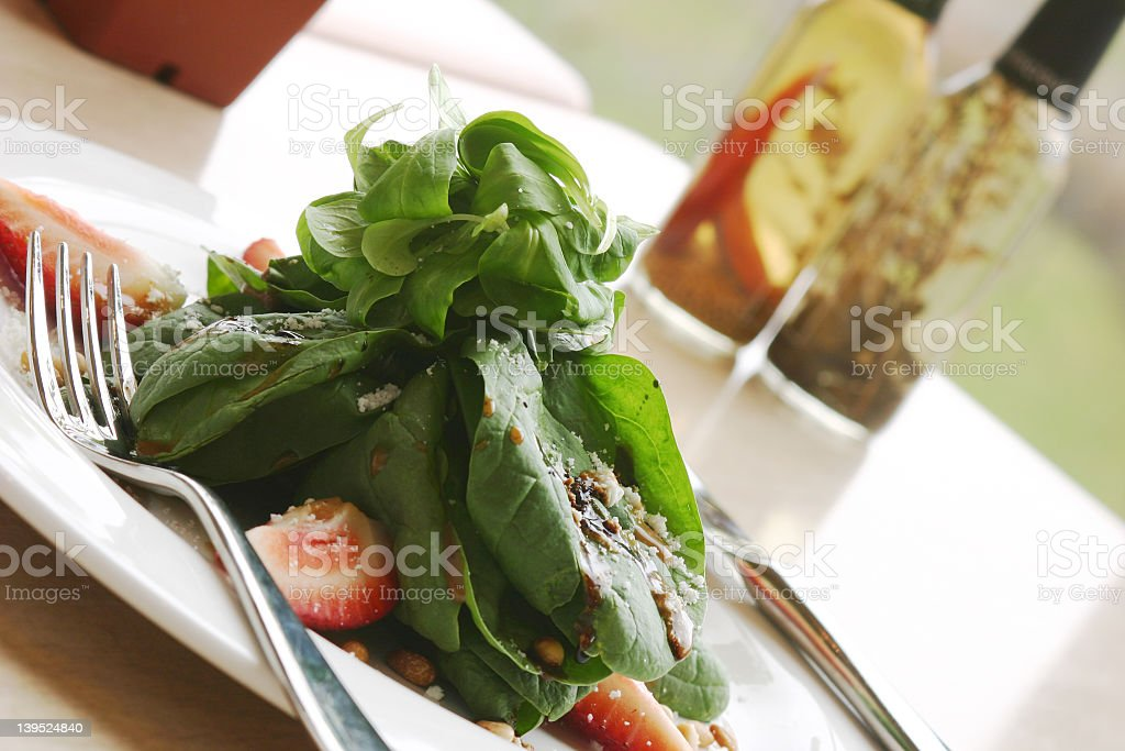 A tasty spinach salad on a white plate royalty-free stock photo