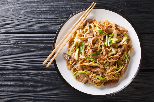 Tasty stir-fried Chinese egg noodles with napa cabbage, green onions and pork closeup in a plate. Horizontal top view stock photo