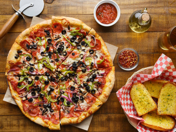 tasty supreme pizza with olives peppers onions and sausage stock photo