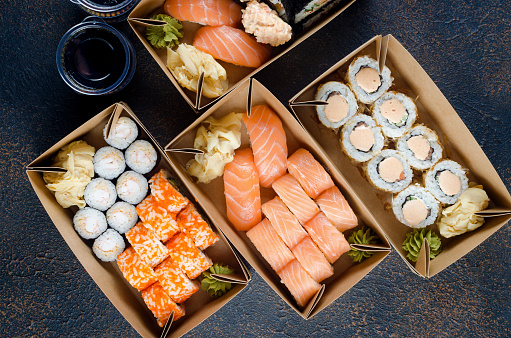 Tasty sushi rolls in disposable kraft paper boxes, sauces on dark table. Concept delivery service Japan food in eco container. flat lay, Template mockup with place for text, Zero waste packaging