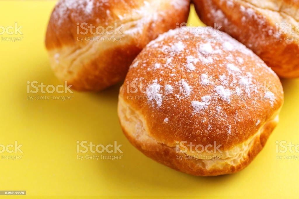 Leckere süße Donuts mit Puderzucker auf leuchtend gelbem Hintergrund – Foto