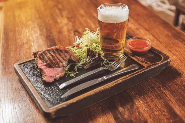 saborosa carne tenra e cerveja gelada no pub - ale - fotografias e filmes do acervo