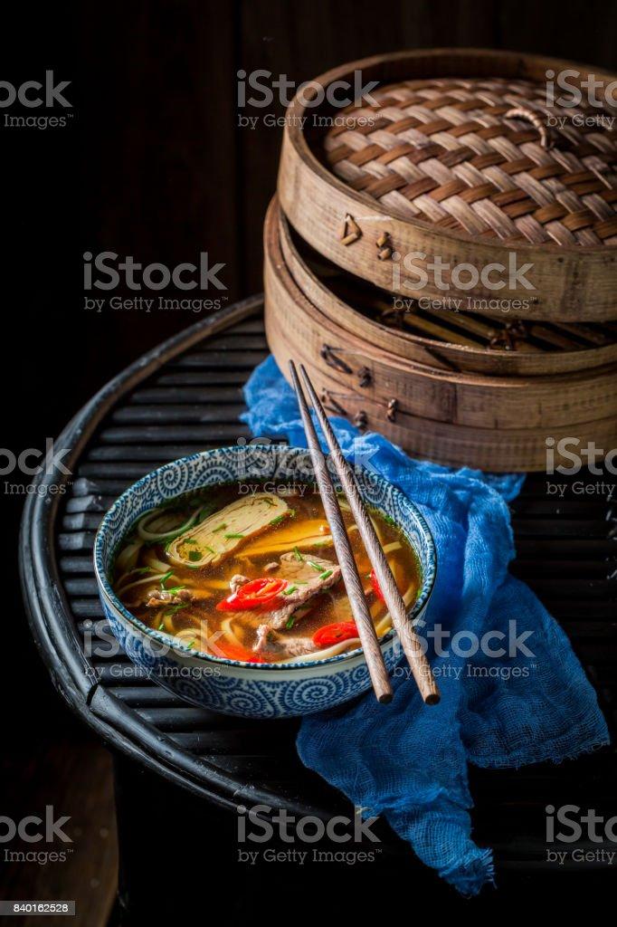 Tasty Thai broth in black bowl on black background stock photo
