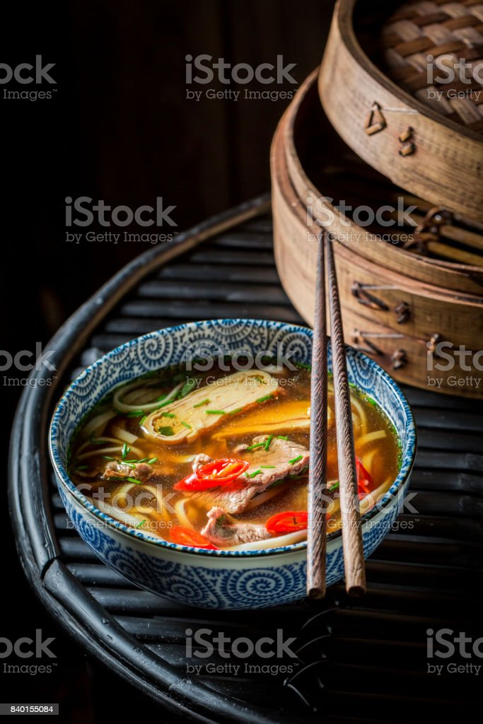 Tasty Thai broth with beef and noodle on black background stock photo