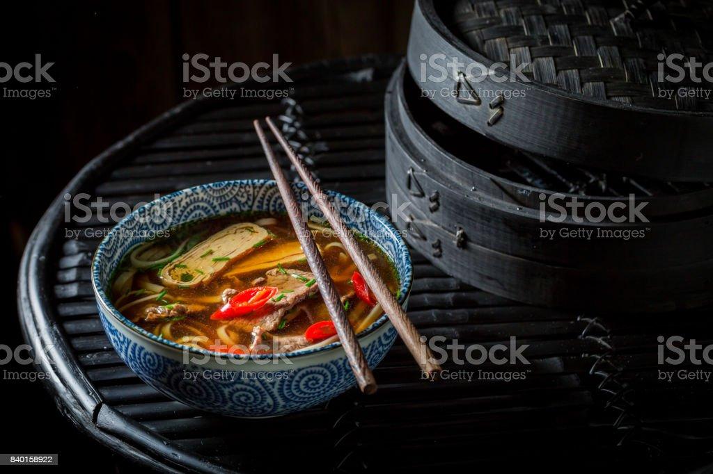 Tasty Thai broth with chopsticks on black background stock photo