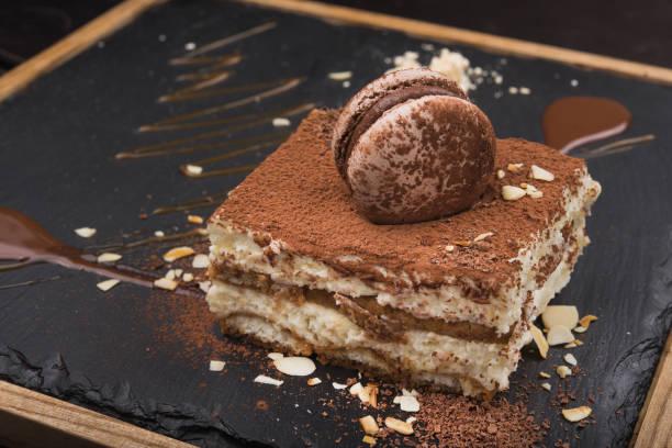pastel de tiramisú delicioso en tablero de pizarra - tiramisu fotografías e imágenes de stock