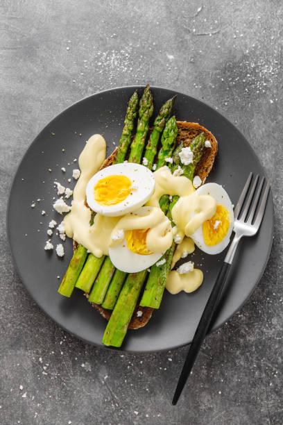 leckere toasts mit spargel, eiern und sauce - sauce hollandaise stock-fotos und bilder