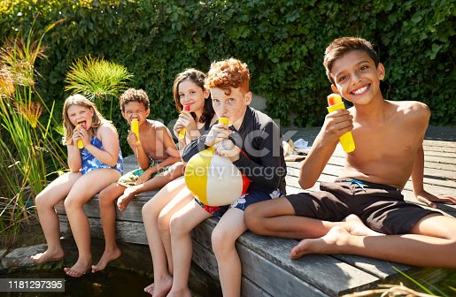 Group of happy children eating ice cream near outdoor pool on a summer day