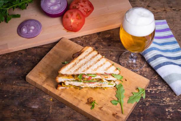 Sanduíche triangular saboroso feito do pão torrado com peito de galinha, bacon fritado, vegetais e vidro da cerveja com espuma em uma tabela de madeira rústica, vista superior - foto de acervo