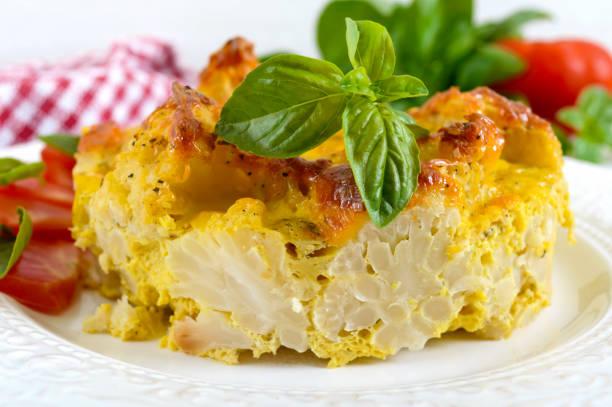 lecker nützlich auflauf aus blumenkohl auf einer platte auf einem weißen hintergrund aus holz. vegetarisches menü. die richtige ernährung. - gebackener blumenkohl stock-fotos und bilder