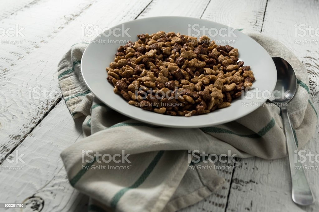 Tasty vanilla and chocolate corn flakes in a white plate on white wooden background, next to a metal spoon on grey kitchen towel stock photo