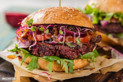istock Tasty vegetarian beet burgers on wooden table 860269338