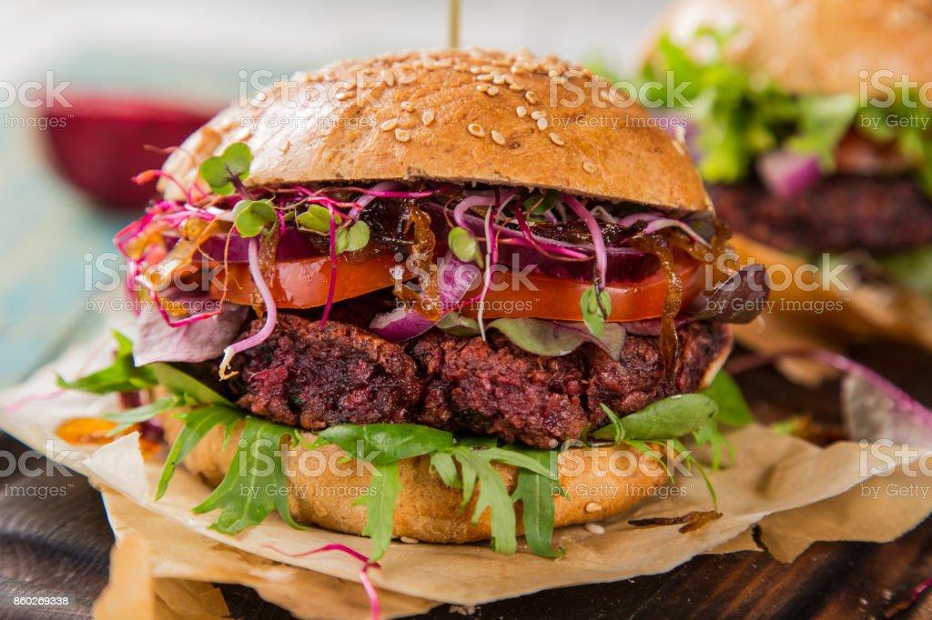 Tasty vegetarian beet burgers on wooden table stock photo