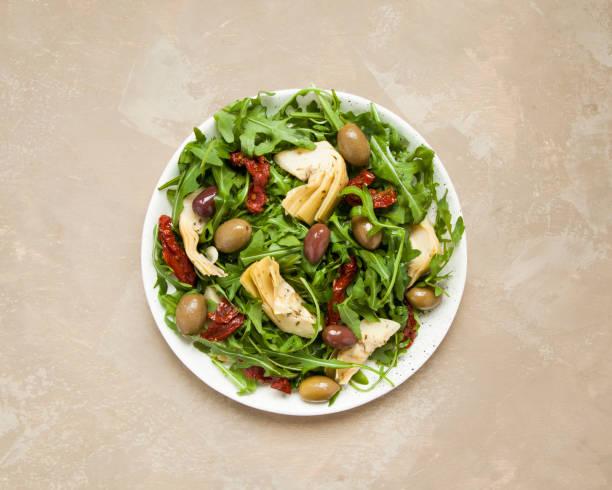 leckere vegetarische salat mit artischocken, rucola, getrockneten tomaten und oliven. - artischocken gesund stock-fotos und bilder