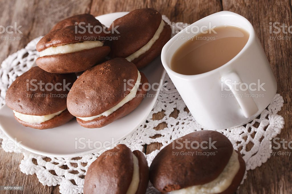 Tasty Whoopie pie and coffee with milk close-up. horizontal stock photo