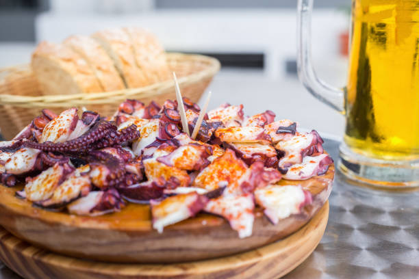 Tasty Wooden plate of galician style cooked octopus with paprika and olive oil. Pulpo a la gallega. Tasty Wooden plate of galician style cooked octopus with paprika and olive oil. Pulpo a la gallega. galicia stock pictures, royalty-free photos & images