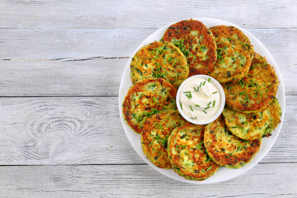 tasty zucchini fritters with sour cream delicious baked in oven zucchini fritters on white plate with sour cream in centre of dish sprinkled with finely chopped chives, healthy and easy vegetarian recipe, view from above fritter stock pictures, royalty-free photos & images