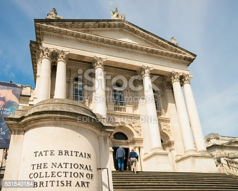 London, UK - May 1, 2016: Close-up of a sign at the foot of the steps leading to the front entrance of the Tate Britain art gallery, with a couple about to enter the building.