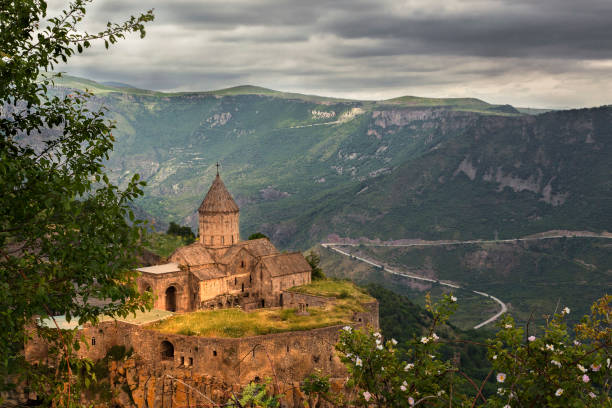Tatev Cathedral in Goris, Armenia. Tatev Cathedral with mountains and a winding road in the background in Armenia. armenian culture stock pictures, royalty-free photos & images