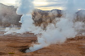 Landscape of the Tatio Geysers with its fumaroles and vapor trails at sunrise, Atacama Desert, Chile.